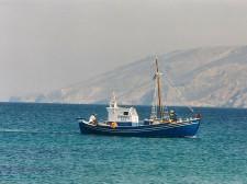Un bateau de pêche passe devant la côte
