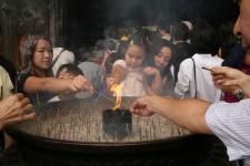 Allumage de bâtons d'encens devant un temple