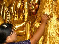 Dépôt rituel d'une feuille d'or sur un Bouddha de la pagode de Shwedagon à Yangon